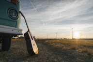 Guitar leaning against camper van in rural landscape with wind turbines at sunset - GUSF01404