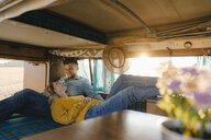 Happy young couple relaxing inside camper van - GUSF01407