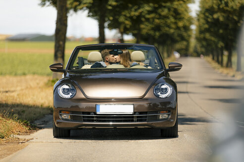 Couple kissing in convertible car on a country road - GUSF01410
