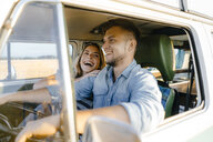 Happy young couple on a trip in camper van - GUSF01419