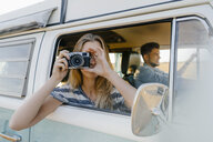 Woman taking picture out of window of a camper van with man driving - GUSF01422