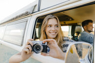 Hhappy woman with camera leaning out of window of a camper van with man driving - GUSF01425