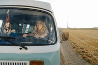 Happy young woman driving camper van in rural landscape - GUSF01431