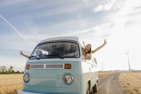 Happy couple leaning out of window of a camper van in rural landscape - GUSF01434