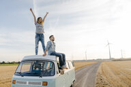 Happy couple on roof of a camper van in rural landscape - GUSF01437