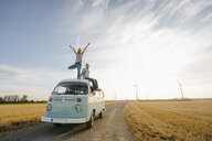 Young couple on roof of a camper van in rural landscape - GUSF01440