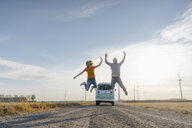 Exuberant couple jumping on dirt track at camper van in rural landscape - GUSF01452