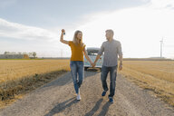 Young couple with car key walking on dirt track at camper van in rural landscape - GUSF01455