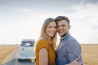 Portrait of smiling young couple at camper van in rural landscape - GUSF01464