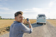 Smiling young man taking cell phone picture of camper van in rural landscape - GUSF01476