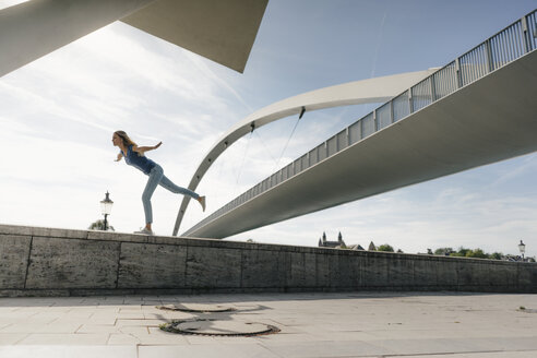 Netherlands, Maastricht, young woman balancing on a wall at a bridge - GUSF01524
