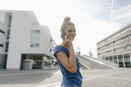 Netherlands, Maastricht, smiling young woman on cell phone in the city - GUSF01530