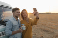 Young couple taking a selfie at camper van in rural landscape at sunset - GUSF01539