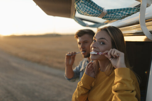 Couple brushing teeth at camper van in rural landscape at sunset - GUSF01542