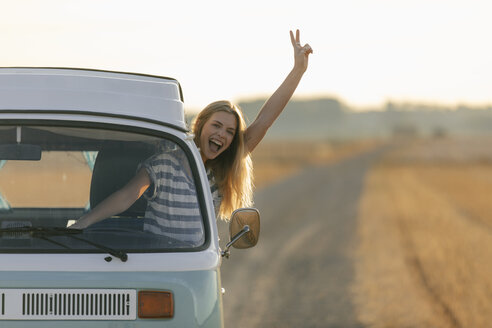 Excited young woman making victory hand sign out of camper van window in rural landscape - GUSF01548