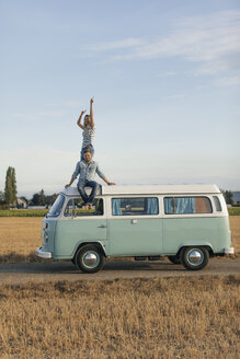 Happy couple on roof of a camper van in rural landscape - GUSF01551