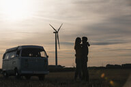 Young couple kissing at camper van at dusk with wind turbine in background - GUSF01557