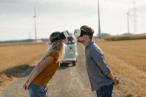 Young couple wearing VR glasses kissing at camper van in rural landscape - GUSF01569