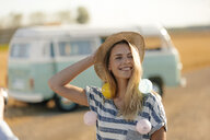 Happy young woman at camper van in rural landscape - GUSF01572