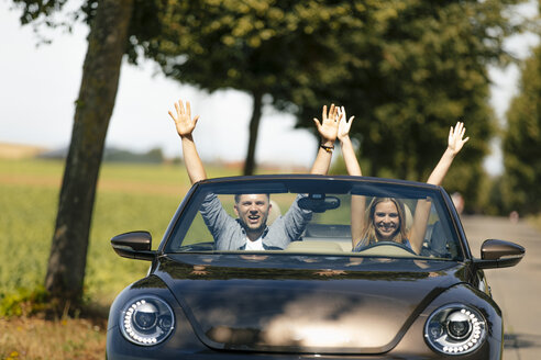 Happy couple driving with raise darms in convertible car on a country road - GUSF01590