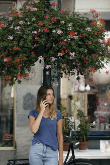 Netherlands, Maastricht, young woman on cell phone at lamp pole in the city - GUSF01599
