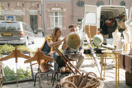 Belgium, Tongeren, young couple examining globe on an antique flea market - GUSF01614