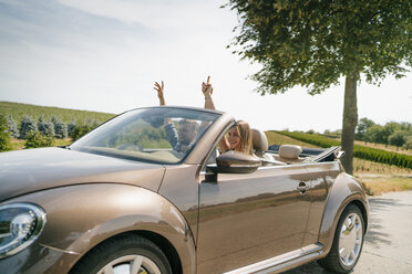 Happy couple driving in convertible car on a country road - GUSF01617