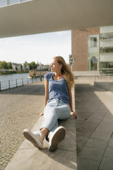 Netherlands, Maastricht, young woman sitting on a wall at the riverside - GUSF01623
