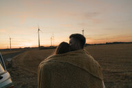 Couple wrapped in a blanket at camper van in rural landscape with wind turbines in background - GUSF01626