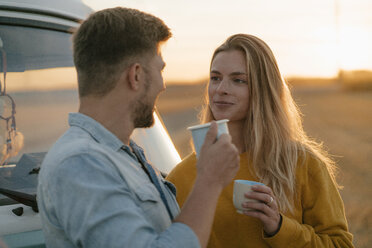 Smiling young couple holding mugs at camper van in rural landscape - GUSF01632
