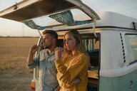 Couple brushing teeth at camper van in rural landscape at sunset - GUSF01635