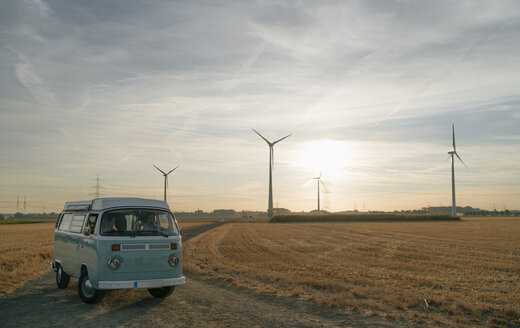 Couple in camper van in rural landscape with wind turbines at sunset - GUSF01638
