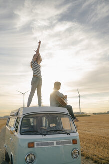 Happy couple with guitar on roof of a camper van in rural landscape - GUSF01644