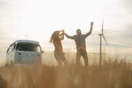 Exuberant couple at camper van in rural landscape with wind turbine in background - GUSF01647