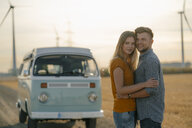 Happy affectionate young couple at camper van in rural landscape - GUSF01650