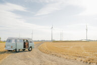 Camper van parked on dirt track in rural landscape with wind turbines - GUSF01653