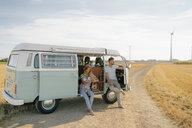 Young couple relaxing in camper van in rural landscape - GUSF01656
