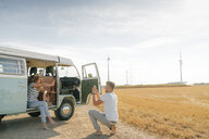 Happy young couple taking cell phone picture at camper van in rural landscape - GUSF01659