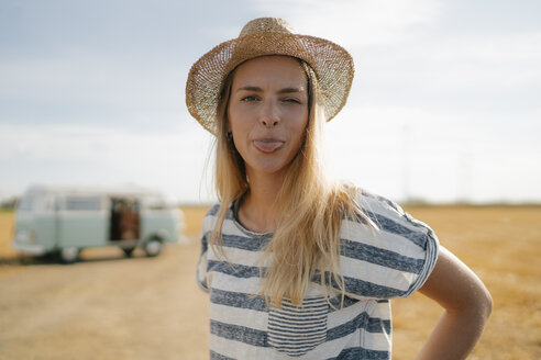 Portrait of young woman at camper van in rural landscape sticking out her tongue - GUSF01662