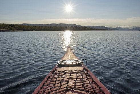 Finland, Lappland, Kilpisjaervi, canoe on lake against the sun - PSIF00160