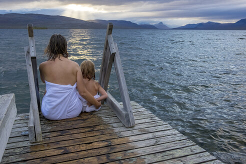 Finland, Lappland, Kilpisjaervi, mother and daughter sitting outside on boardwalk, rear view - PSIF00163