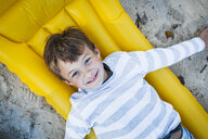 Portrait of smiling little boy lying on yellow airbed on the beach in autumn - HMEF00080