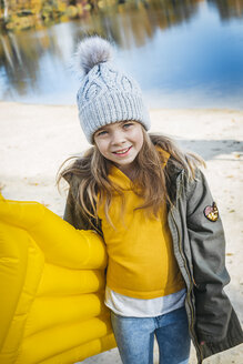 Portrait of smiling girl with yellow airbed at lakeshore in autumn - HMEF00083