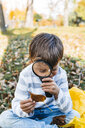 Little boy exploring autumn leaf with magnifying glass in nature - HMEF00092
