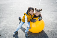 Two little children having fun with gym ball - HMEF00095