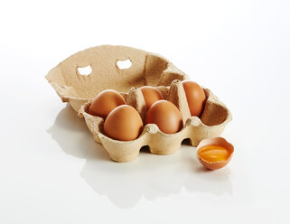 Egg box with brown eggs and an opened egg on white background - KSWF01988