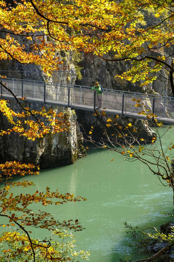 Austria, Tyrol, hiker on suspension bridge looking at Tiroler Ache in autumn - LBF02253 - Lisa und Wilfried Bahnmüller/Westend61