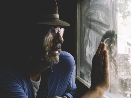 Man with a beard, hat and glasses posing next to a window. - OCMF00114