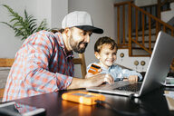 Father and son using laptop together, online shopping - JRFF02000