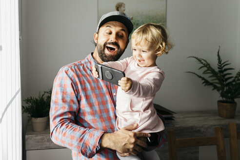 Father holding his little daughter on his arm, playing with his smartphone - JRFF02003